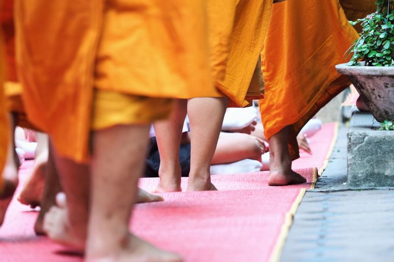 Low section of monks walking on red carpet