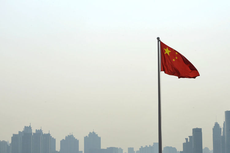 Chinese flag in city against clear sky