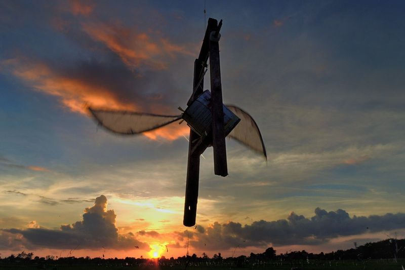 Low Angle View Of Blades Rotating Against Sky During Sunset