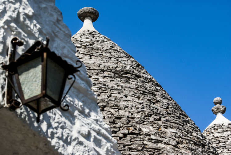 The magic of Alberobello's Trulli travel location - It was really amazing to know this particulars constructions full of charming and to ear the history about the Alberobello's Trulli in the Italy Apulia region (Puglia). The history said that the Alberobello's origins date back to the Middle Age. The settlers built the houses with stone and without cement and with the easiest way to demolish them in the case of an inspection by the Kingdom of Naples, thus avoiding paying taxes. Another interesting thing is the decorative pinnacles and symbols painted on many roofs of the trulli that were often used to identify the different religions of their inhabitants. Albelobelo Italia Viajes  2019 EyeEm Awards The Traveler - 2019 EyeEm Awards The Architect - 2019 EyeEm Awards The Photojournalist - 2019 EyeEm Awards The Street Photographer - 2019 EyeEm Awards Italy EyeEm Gallery EyeEm Best Shots Eyeem4photography Low Angle View Sky Architecture No People Built Structure Day Building Exterior Nature Blue Clear Sky Building History Solid The Past Spirituality Belief Religion Place Of Worship Stone Material Art And Craft Outdoors
