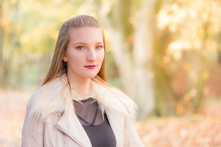 Portrait of young beautiful woman standing against autumn trees