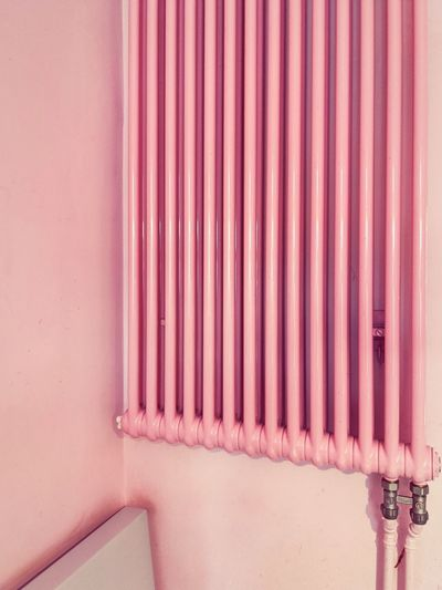 Close-up of pink radiator pipes on wall in building