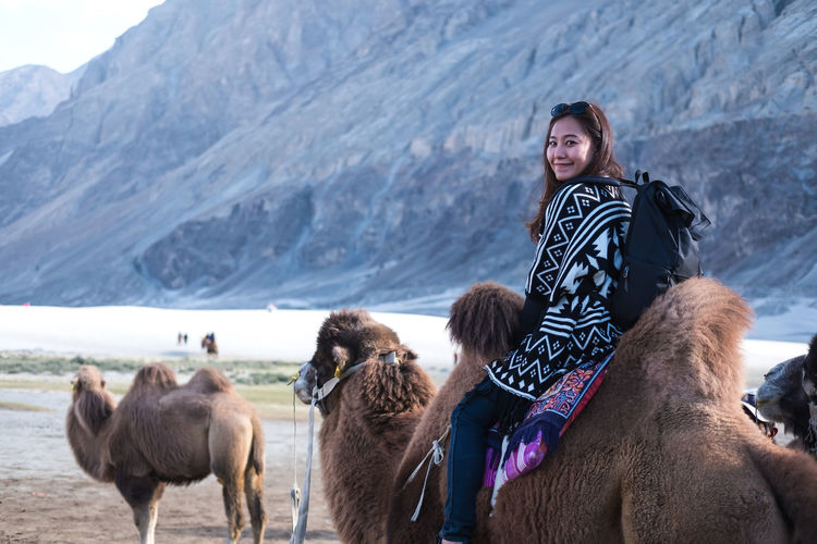 A beautiful Asian tourist woman riding camel in the Hunder desert , Ladakh India Landscape Animal Happy Asian  Journey Nature Beautiful Back Trip Desert Joy Young Lifestyle Traveler Lady Thai Smile Summer Holiday Culture Sand Ride Caravan Leisure Destination Adventure Safari Vacation Camel Tourism Transportation Woman Indian Girl Tourist ASIA Traditional Female People Sunny Dune Travel Mammal Park Fun Experience India Outdoor