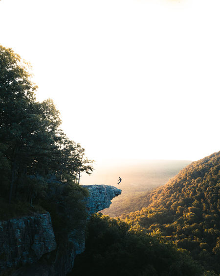 Person on mountain against sky