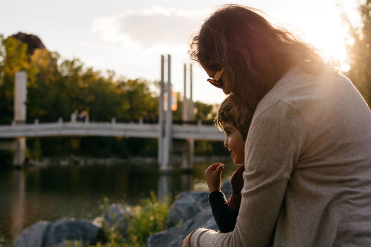 Side view of woman sitting with son by lake