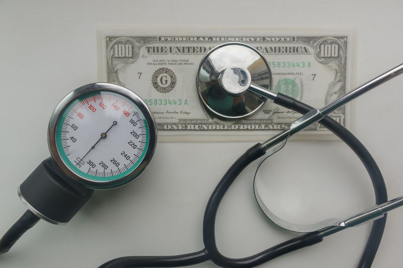 High angle view of stethoscope with pressure gauge and currency on table