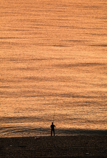 Silhouette man fishing while standing at shore during sunrise