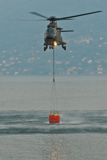 Helicopter Air Vehicle Airplane Day Fire Department In Action Flying Helicopter Horizon Horizon Over Water Illuminated Mode Of Transportation Motion Nature Nautical Vessel No People Outdoors Sea Sky Transportation Water Waterfront