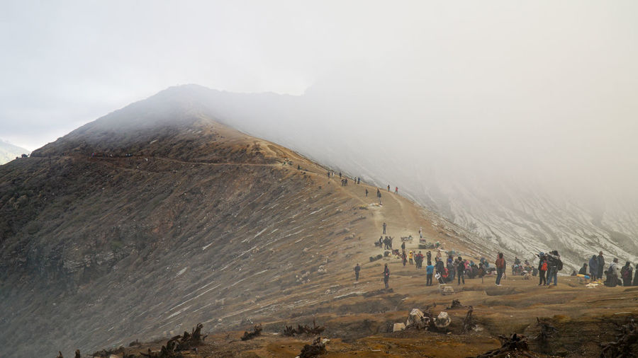 Crowd of people on hill against fog