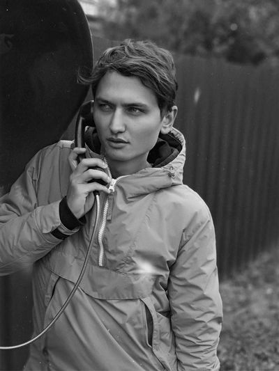 Young man holding telephone on footpath