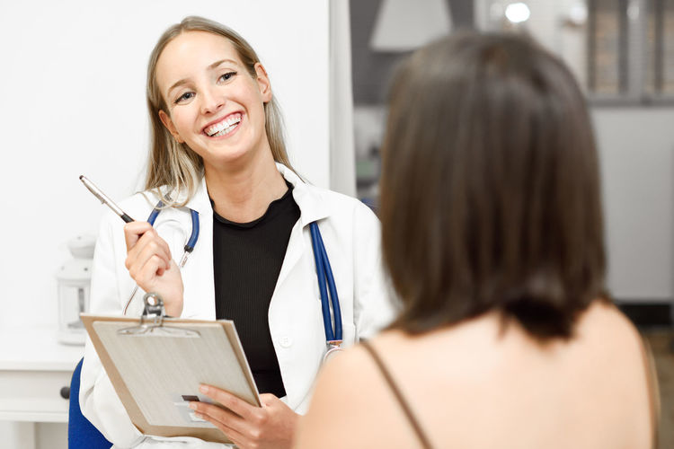 Smiling female doctor having discussion with patient at clinic