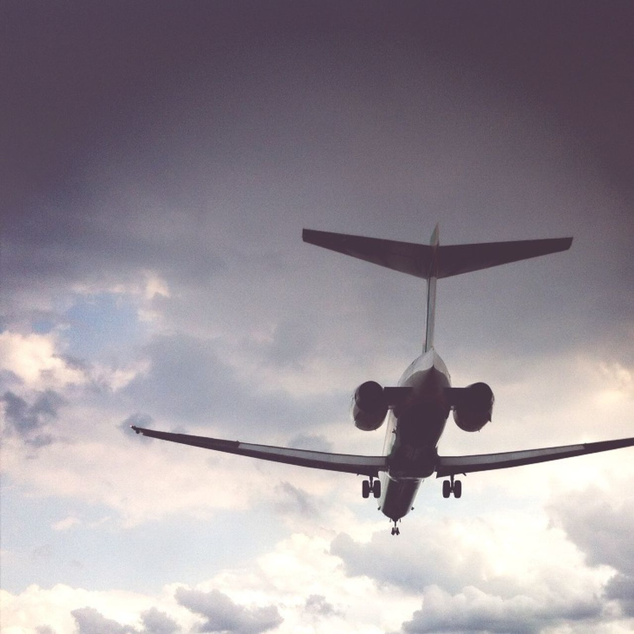 View of airplane in flight against clouds