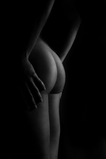 Midsection of naked woman standing against black background