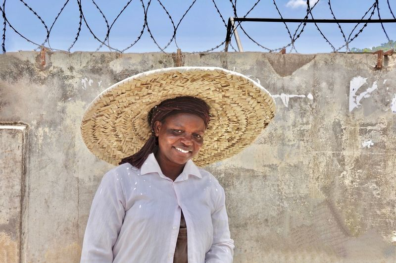 Portrait of smiling woman wearing straw hat against wall