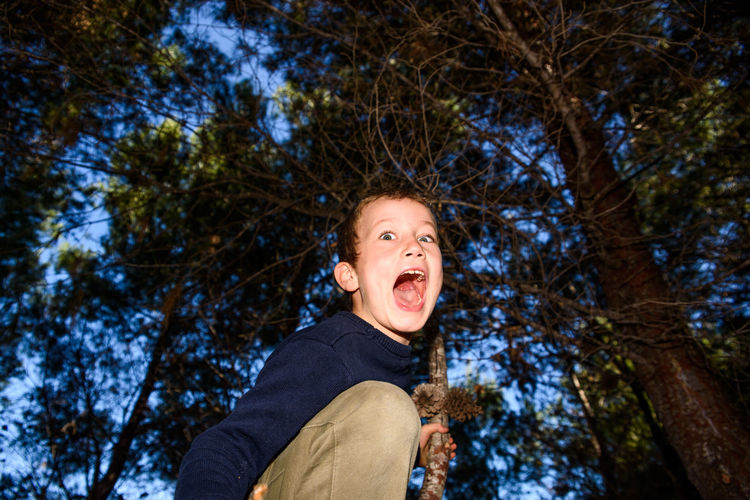 Low angle portrait of boy against trees