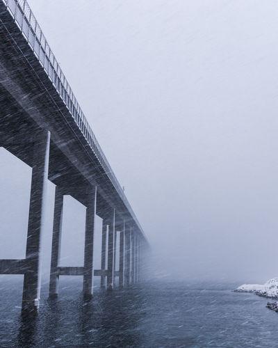 Silhouette bridge over sea against clear sky