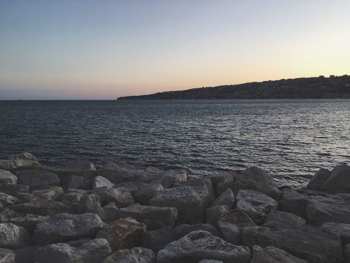 Water Sea Nature Beauty In Nature Tranquil Scene Sunset Tranquility Scenics Clear Sky Outdoors Copy Space No People Rock - Object Sky Beach Horizon Over Water Pebble Beach Day