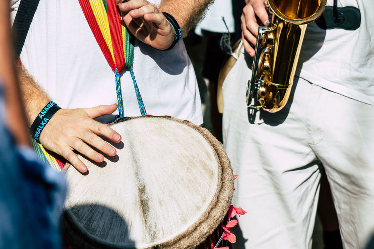 Midsection of people playing saxophone and drum