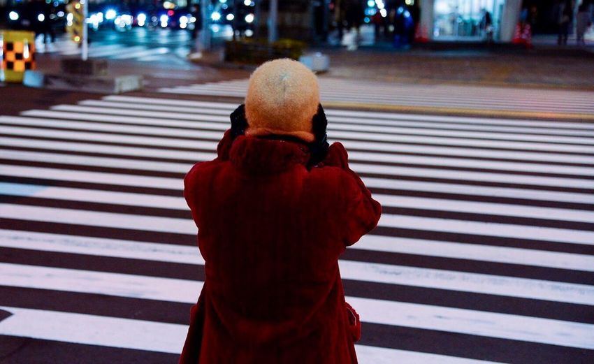 Rear view of a woman crossing road