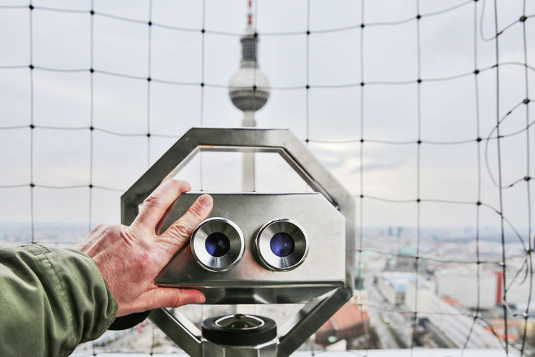 Close-Up Of Man Holding Coin-Operated Binoculars Against Fernsehturm