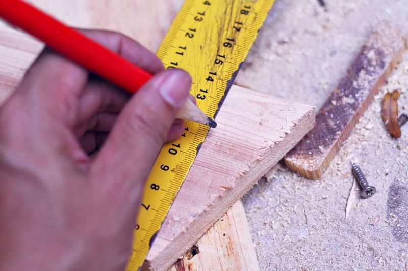 Carpenter marking on wooden Human Hand Tape Measure Hand Close-up Instrument Of Measurement Accuracy Human Body Part Holding