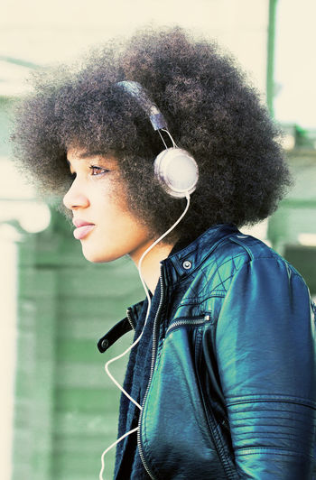 Close-up portrait of young woman listening music through headphones