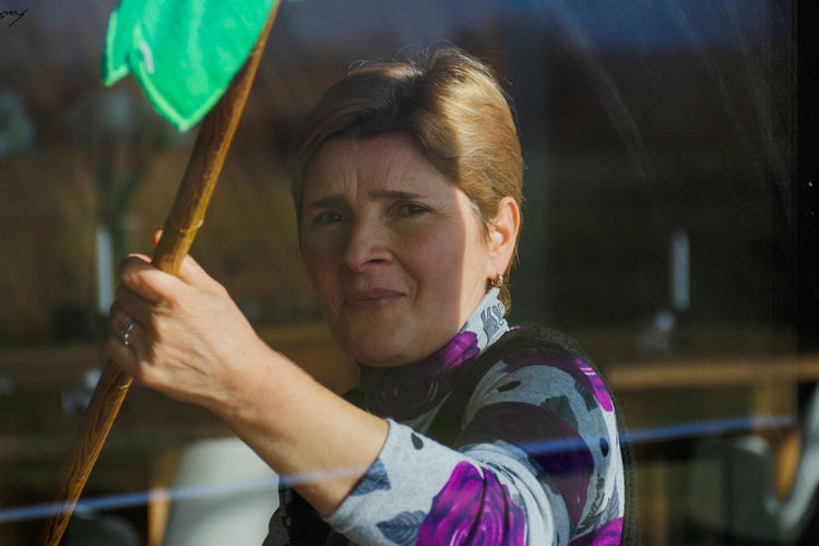 Close-up portrait of woman holding stick seen through window