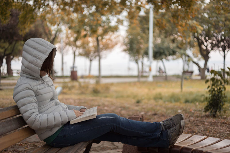 Woman reading book on bench at park