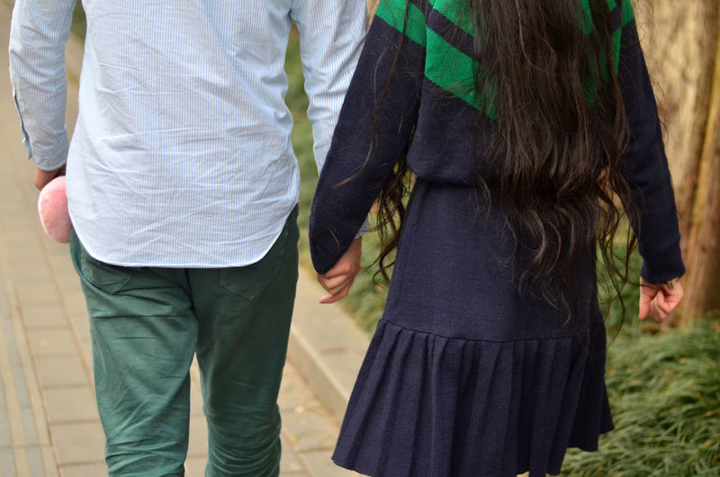 Midsection Of Couple Holding Hands While Walking On Footpath