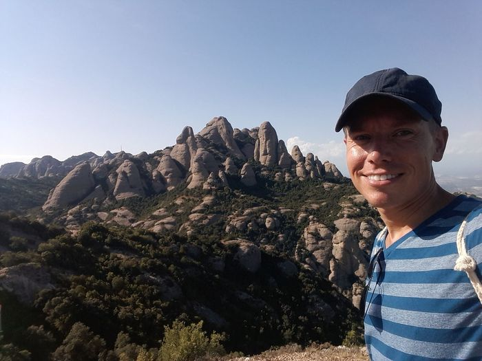 Portrait of man smiling while standing against mountains
