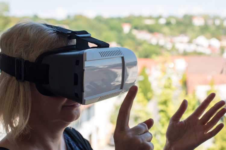 Close-up of senior woman gesturing while using virtual reality simulator