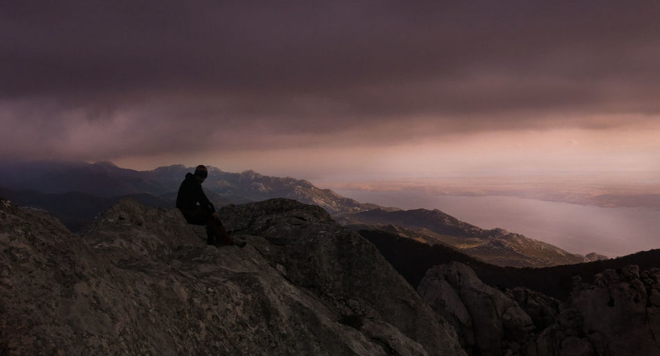 Silhouette woman sitting on mountain against sky during sunset