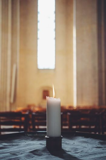 Close-up of burning candle in church