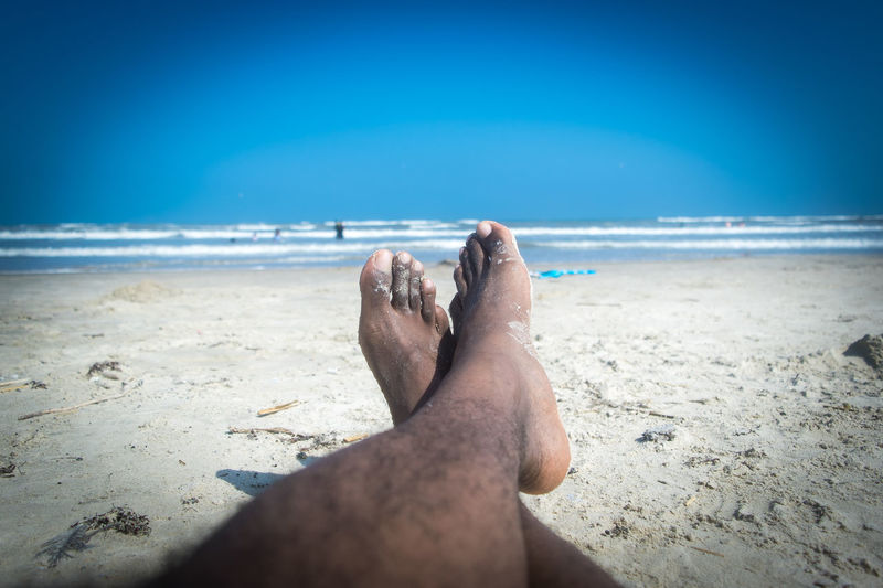 Low section of man relaxing on sand at beach against blue sky