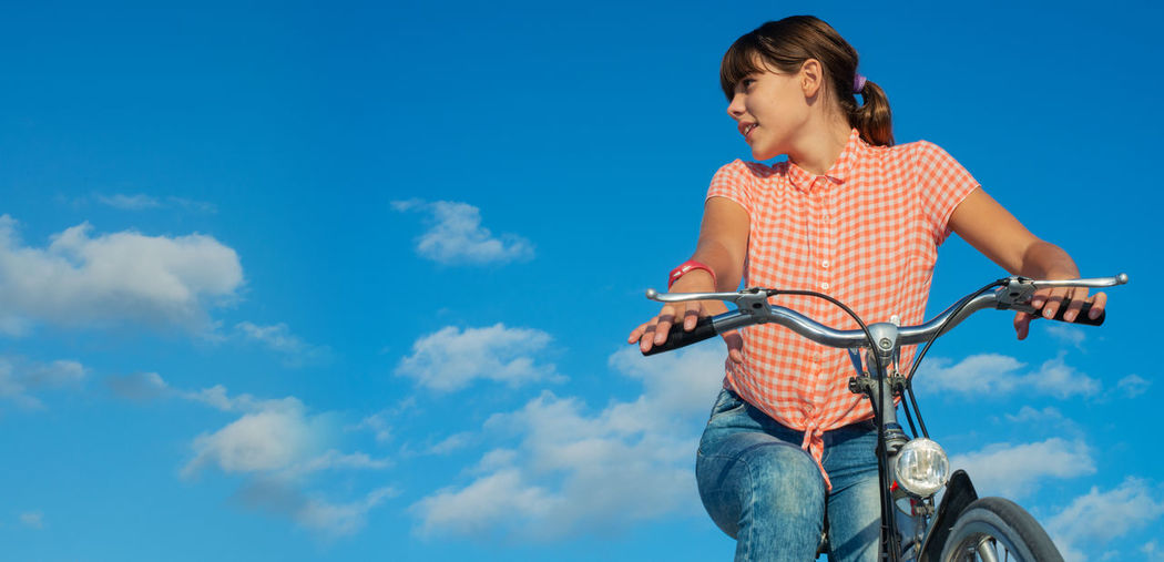 Low angle view of girl riding bicycle against blue sky