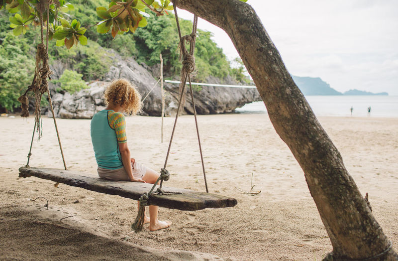Full length of woman sitting on swing at beach