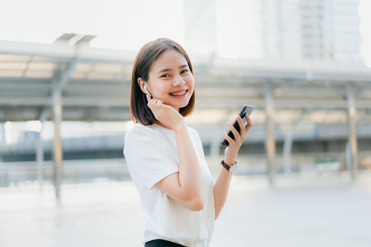 Women are listening to music from white headphones. And using hands touch to use various functions, happy mood. One Person Smiling Communication Wireless Technology Mobile Phone Holding Technology Young Adult Women Happiness Looking At Camera City Connection Portrait Adult Smart Phone Architecture Focus On Foreground Day Hairstyle Outdoors