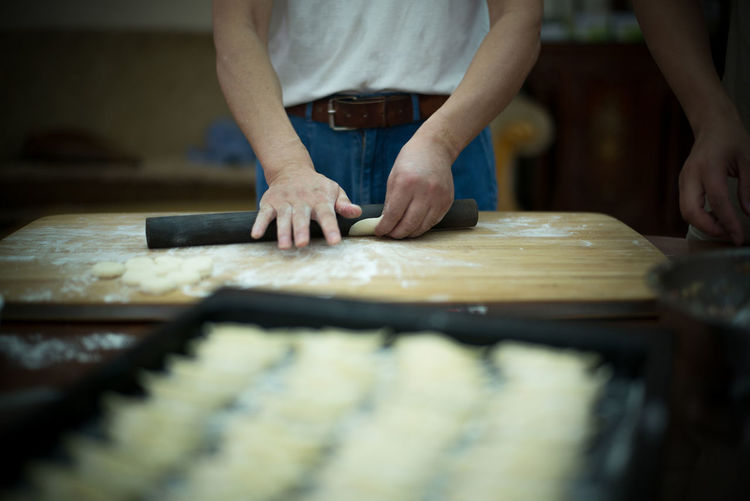 Midsection Of Man Rolling Dough At Table