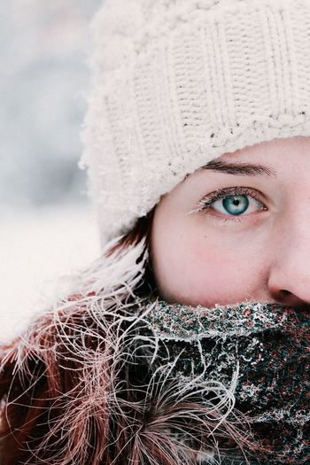 Close-up portrait of woman in hat during winter