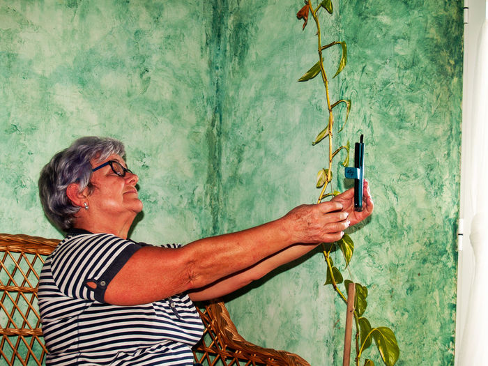 Side View Of Smiling Senior Woman Taking Selfie At Home