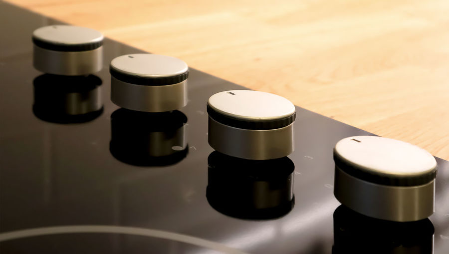 Selective focus on adjustable knobs of kitchen appliance gas stove on wooden top table background. Arts Culture And Entertainment Beauty Product Black Color Chemistry Close-up Focus On Foreground High Angle View Indoors  Industry No People Reflection Research Science Shadow Still Life Table Technology White White Color Wood - Material