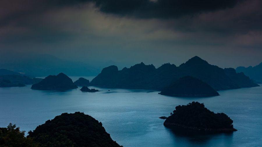 Rocks in sea against sky at dusk