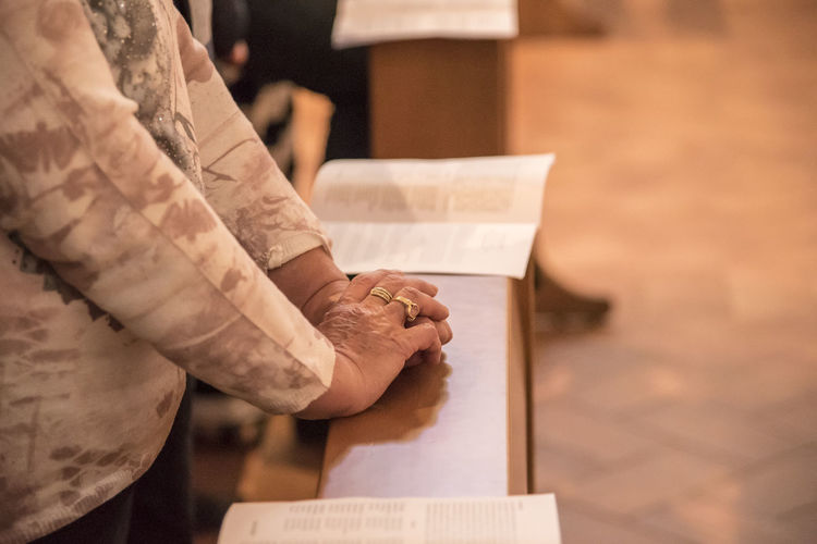 Closeup of an old woman's hands joined , focus on hands Art And Craft Close-up Focus On Foreground Hand Holding Human Body Part Human Hand Indoors  Lifestyles Men Midsection Occupation One Person Paper Real People Standing Table Women Wood - Material