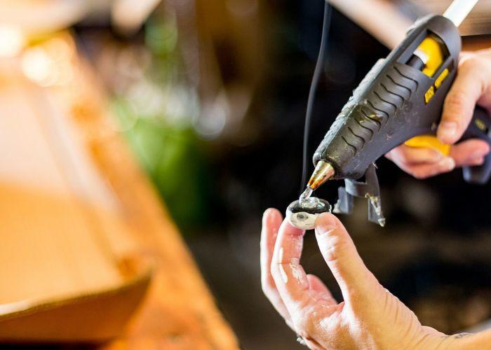 Cropped image of man holding glue gun at workshop