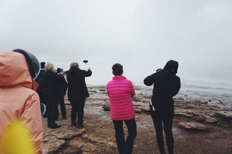 Rear view of people standing by geyser strokkur iceland against sky