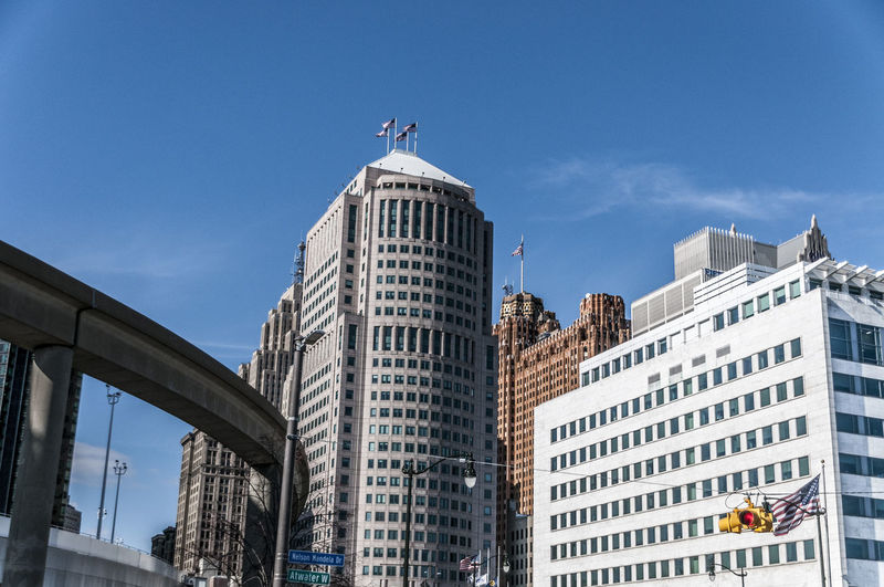 Low angle view of buildings and monorail against blue sky