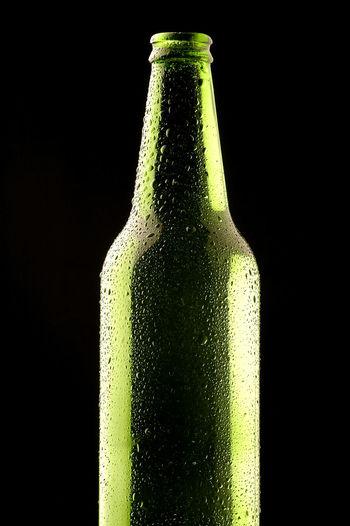 Close-up of green bottle against black background