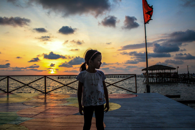 Magnificent sunset by the seashore, silhouette of a little girl stands by a floating platform, sea breeze, a fluttering flag combo with a mini hovel as the backdrop. This is a small harbour, consists of ±400 people which majority of them are fishermen. Sky Sunset Water Cloud - Sky One Person Real People Standing Sea Flag Beauty In Nature Leisure Activity Lifestyles Scenics - Nature Nature Women Orange Color Beach Three Quarter Length Outdoors
