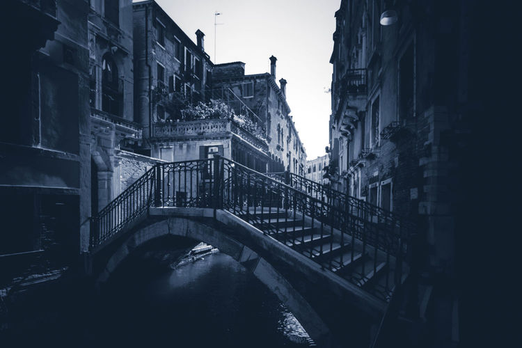 Bridge over canal amidst buildings against clear sky