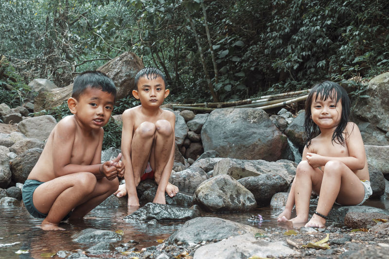 Full length cute kids sitting by rocks in forest